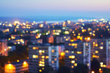 Blurred view from a bird's eye view to a modern night city. Bright lights of high buildings of urban residents