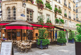Fototapeta Paris - Typical view of the Parisian street with tables of brasserie (cafe) in Paris, France