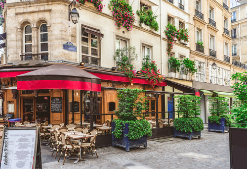 plakat Typical view of the Parisian street with tables of brasserie (cafe) in Paris, France