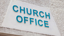 Church Office Sign. Blue Text On A White Textured Wall.