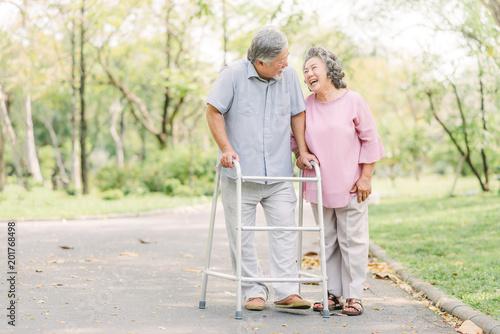 Fototapeta Happy senior couple talking a walk with walker obraz