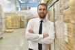 canvas print picture - Portrait lächelnder Geschäftsmann/ Unternehmer im Warenlager einer Spedition // Portrait of a smiling businessman/ entrepreneur in the warehouse of a forwarding agency
