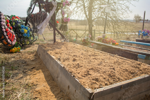 Fotografie, Obraz  photo of a fresh grave, which is ennobled by a graveyard worker
