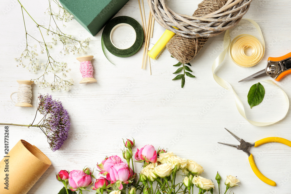Fototapeta Florist equipment with flowers on wooden background, top view