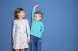 canvas print picture - Little girl and boy measuring their height on color background