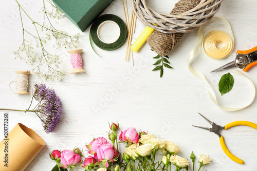 Photo Florist equipment with flowers on wooden background, top view