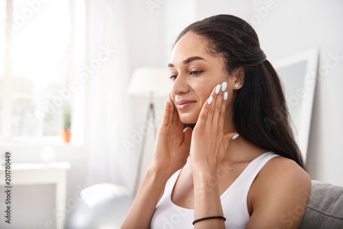 Poster Spa Anti-ageing massage. Beautiful dark-haired young woman rubbing her cheeks with her fingers while doing a facial massage