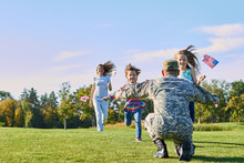 Soldier Is Meeting His Family Outdoors. Happy Reunion Of Father And Kids On The Grass.