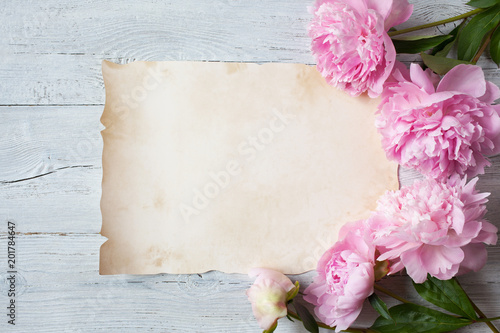 Pink peonies on a wooden background and a sheet of paper for congratulations, invitations
