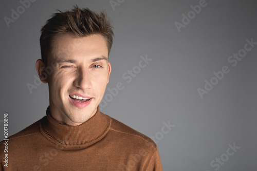 Fotografie, Obraz  Portrait of handsome guy with trendy hairstyle winking at camera