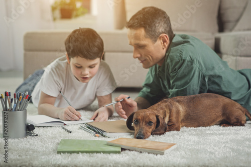 Fotografie, Obraz  Focus on dachshund puppy getting bored while her owners are involved in doing homework