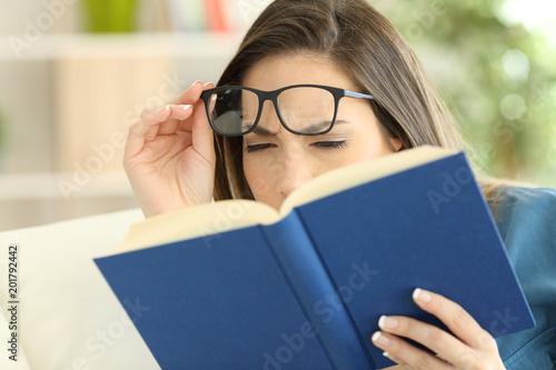 Fotomural Woman suffering eyestrain reading a book