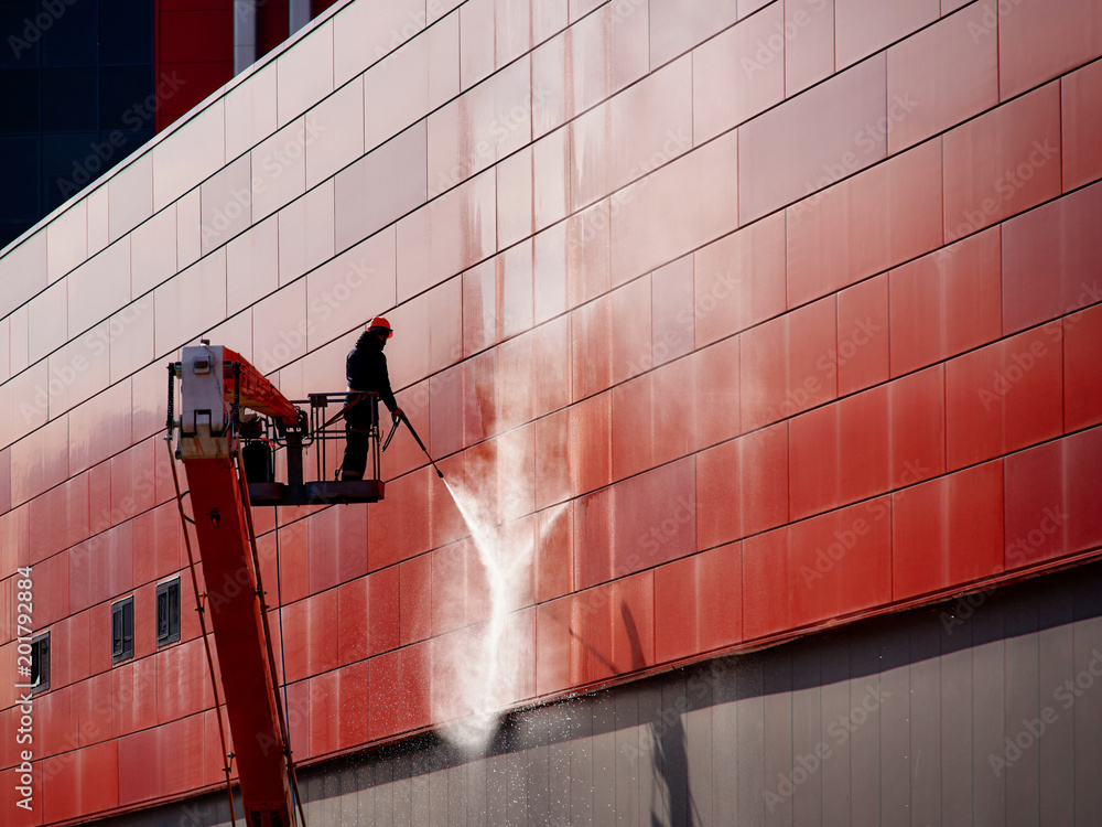 Fototapeta Worker wearing safety harness washes wall facade at height on modern building in a crane.