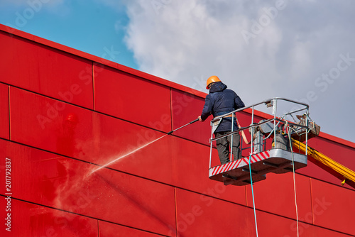Fotografia, Obraz Worker wearing safety harness washes wall facade at height on modern building in a crane