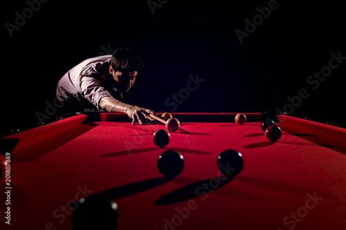 Leinwand Poster A man with a beard plays a big billiard.