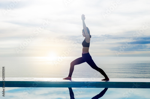 Staande foto Ontspanning Asian young woman practice yoga Warrior I or Virabhadrasana Pose on the beach with beautiful sea,Feeling so comfortable and relax in holiday