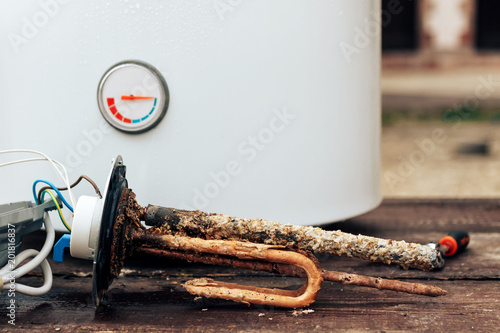 Photo heating element, rust and scale on boiler background, lying on wooden table
