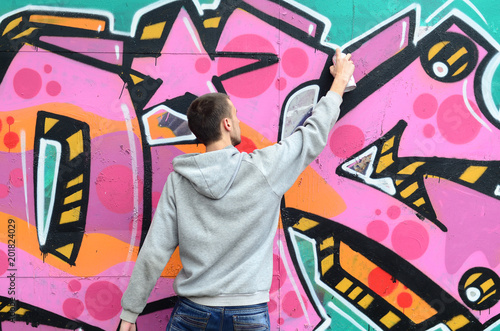 plakat A young guy in a gray hoodie paints graffiti in pink and green colors on a wall in rainy weather