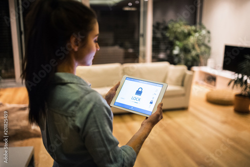 Fotografía  A woman holding a tablet with smart home screen.