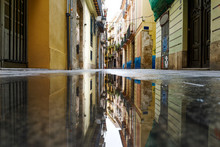 Valencia, Spain - Street In The Old Town And Buildings Reflection In A Puddle