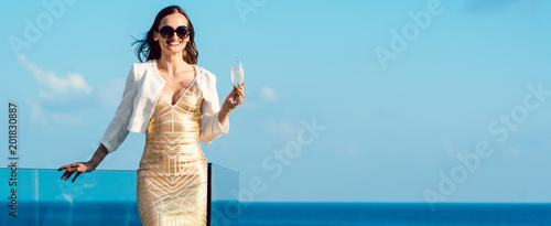 Deurstickers Droogte Woman drinking sparkling wine looking over ocean wearing an expensive dress