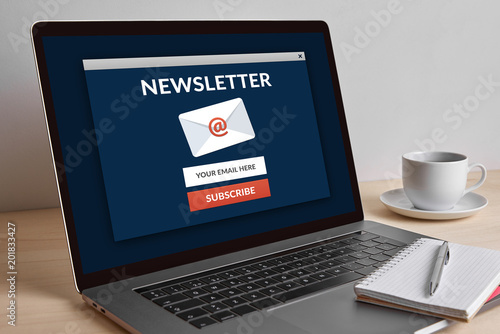 Subscribe newsletter concept on modern laptop computer screen on wooden table. All screen content is designed by me.