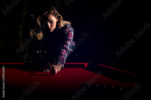 Young woman playing billiards in the dark billiard club Wallpaper Mural
