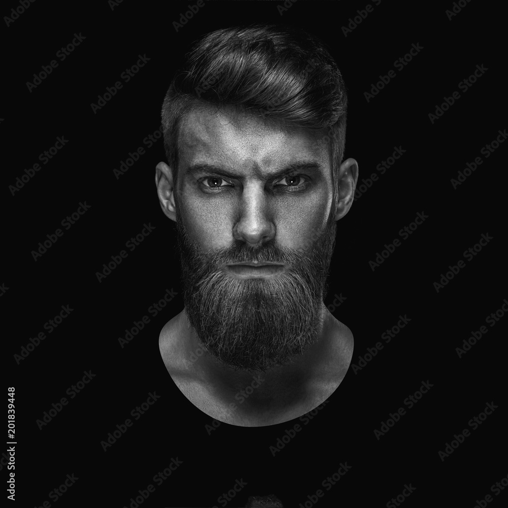 Fototapeta Black and white portrait of serious young man Isolated on black background and looking at camera Confident concept