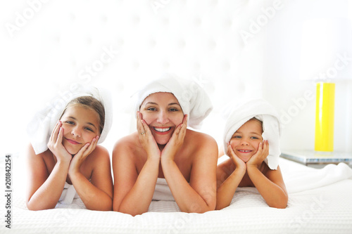Keuken foto achterwand Spa Mother and girls in bathrobes in room after shower