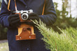 Woman's hand in black gloves holding retro photo camera outdoor. Lifestyle concept with autumn nature on background. Close-up