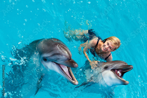 Coach swims in the water with dolphins. Dolphin Assisted Therapy.