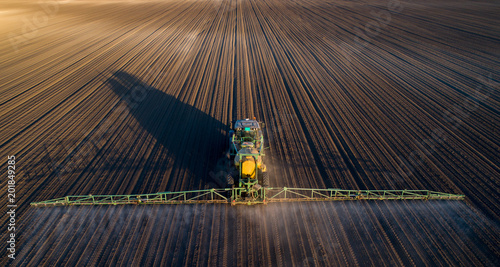 Tractor spraying soil in field