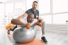 Physical Activity. Serious Professional Trainer Looking At His Client While Monitoring How He Does Physical Activity