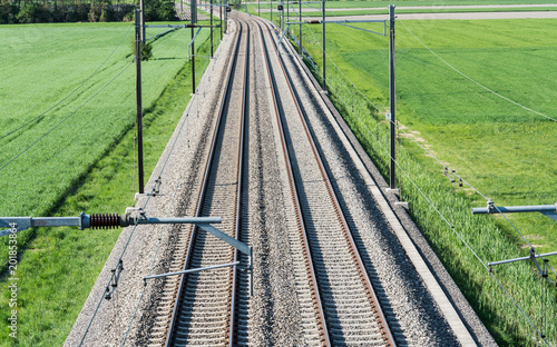 several railroad tracks leading to the horizon in midst of green fields