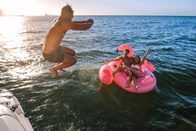 Man Diving In Sea With Friends On Inflatable Toy