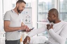 Description Of Symptoms. Pleasant Young Man Talking To His Doctor While Describing Symptoms