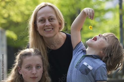 Valokuva Pequeño niño haciendo un gesto de introducir en su boca una flor, junto a él  y sin darse cuenta de lo que está haciendo se encuentra sus sonrientes madre y hermana mayor