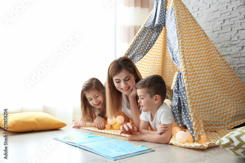 Nanny and little children reading book in tent at home Canvas Print