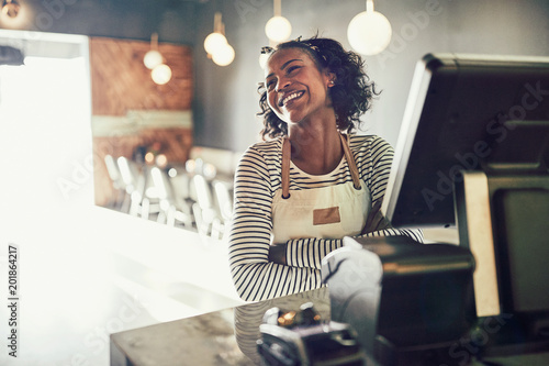 Valokuva  Young African waitress standing at an order terminal and laughin