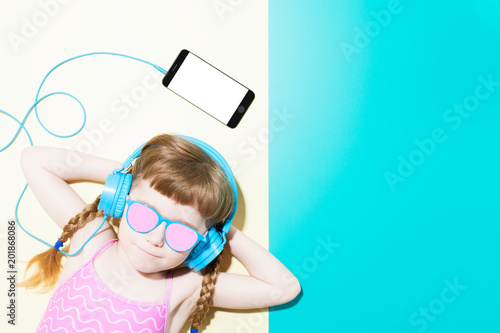 Poster Magasin de musique Little girl in swimsuit listening to music