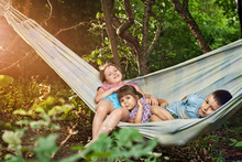 Children Play In A Hammock In The Summer