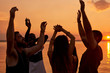 Cheerful positive young friend dancing in light of sunset enjoying beach party and their gathering on vacation