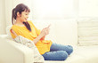 people, technology, communication and leisure concept - happy young asian woman sitting on sofa and texting message on smartphone at home