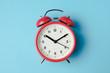 canvas print picture - Red vintage alarm clock on light blue color background