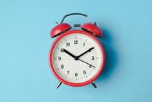 Red Vintage Alarm Clock On Light Blue Color Background