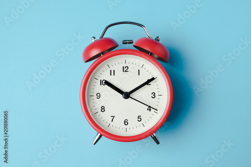 Red vintage alarm clock on light blue color background Fototapeta