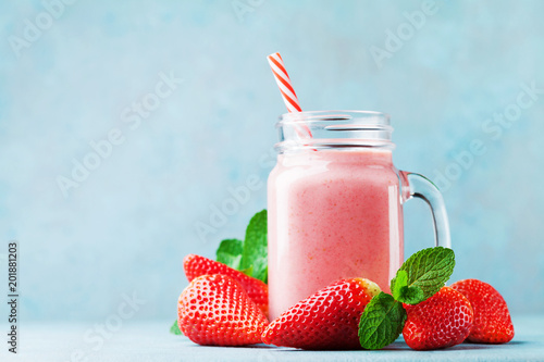 Pink strawberry smoothie or milkshake in mason jar on blue table. Healthy food for breakfast and snack.