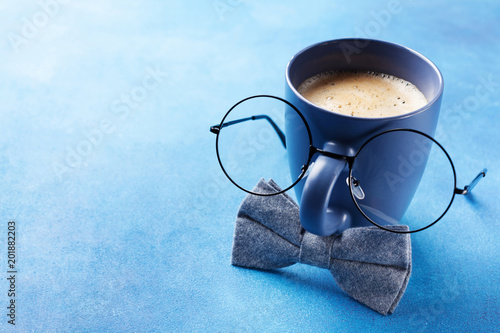 Creative breakfast on Happy Fathers Day with funny face from cup of coffee, eyeglasses and bowtie.