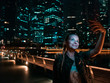 Woman holding smartphone for self-portrait photo with view of modern skyscrapers at night