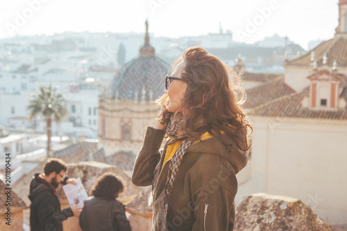 Beautiful young women looking far from the top (Castle) of a typical Spanish town (Carmona) on sunset